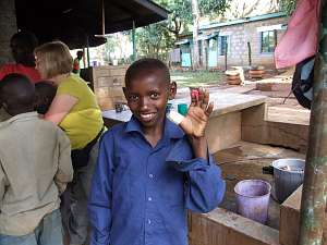 A young boy shows off his injured thumb