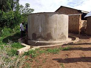 A cylindrical concrete water tank with corrugated metal roof
