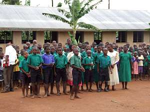 Children, many of them in green shirts and dresses, line up outside Mugungulu School