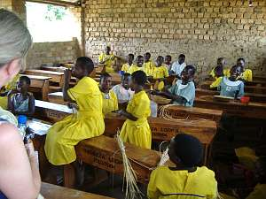 School children, many of them in bright yellow uniforms, in their classroom at Kyamukoona School