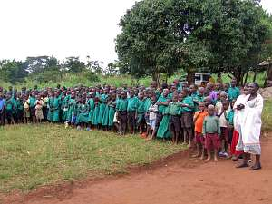 A large group of children, girls mainly in green dresses and boys in green shirts and shorts, line up for a welcome reception at Mugungulu School