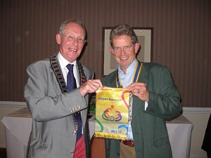 District Governor Niall Blair (left) presents President Chris Le Fevre with this year's International Banner